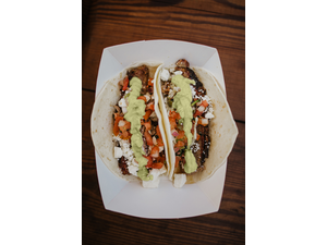 Picture of Pork Tacos- 2 flour tortillas topped with pulled pork, feta, pico, and avacado cilantro cream sauce and served with a drink